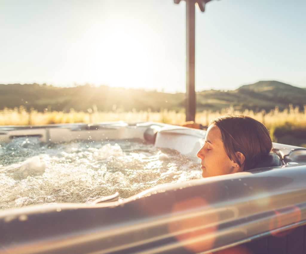 Woman in whirlpool jacuzzi at sunset